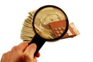 בחינה של כסף עם זכוכית מגדלת - תמונת אילוסטרציה